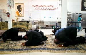 "In the bakery's kitchen where symbols of their Muslim faith are worn on the walls, the Brothers take part in a cleansing prayer called the ""Rakas Salat"" which is done in the kneeling position. (Nancy Pastor/Oakland Tribune)"